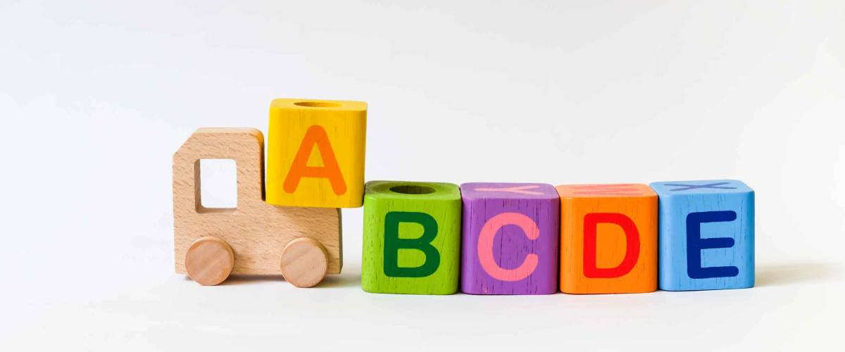 Wooden ABC Blocks and Wooden Car Toy on gray background with copyspace