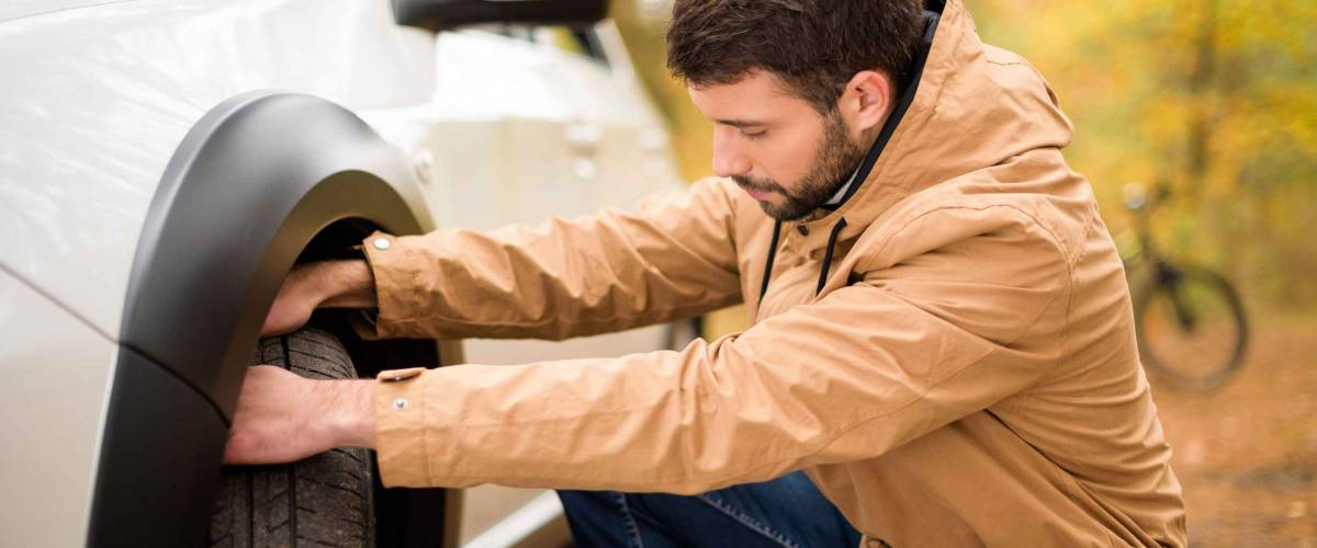 Young bearded man checking car tire in autumn forest