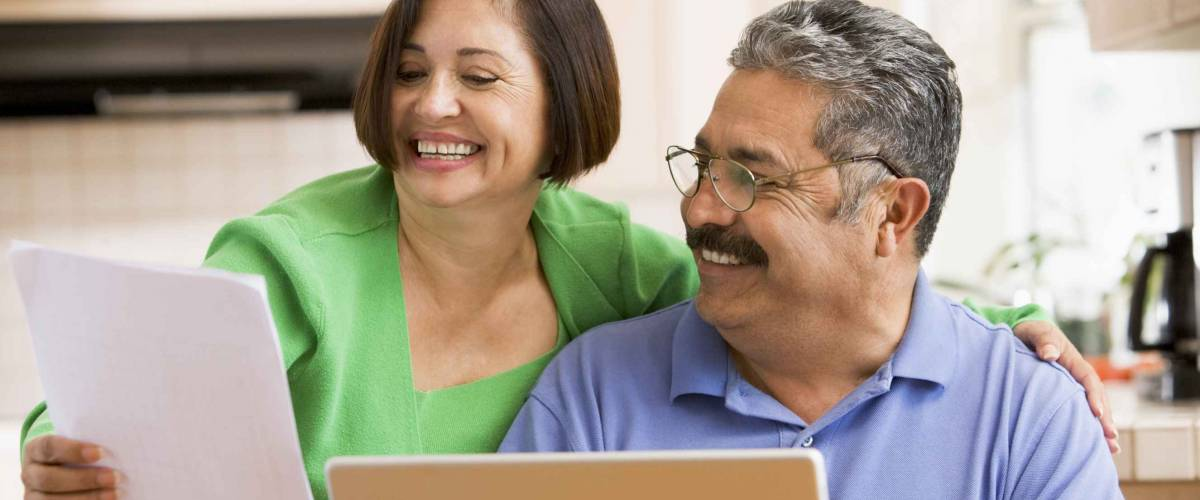 Couple in kitchen with laptop and paperwork smiling