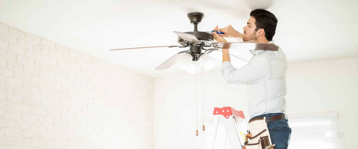 Profile view of a male electrician stepping on a ladder and installing a ceiling fan in a house