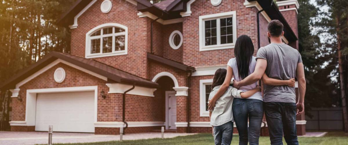 Back view of happy family is standing near their modern house and hugging