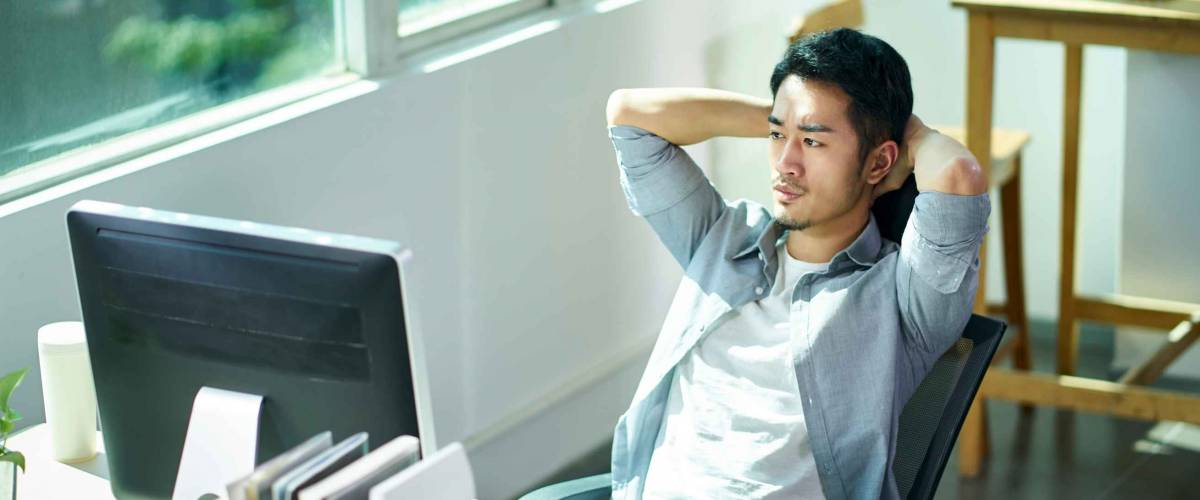young asian business man entrepreneur contemplating in office, hands behind head frowning.