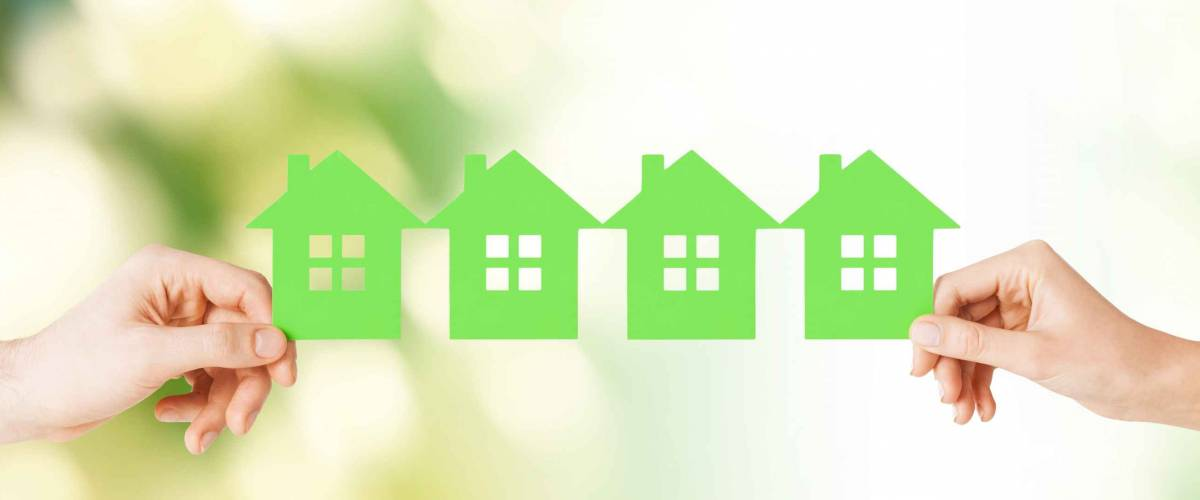 real estate and family home concept - closeup picture of male and female hands holding many green paper houses