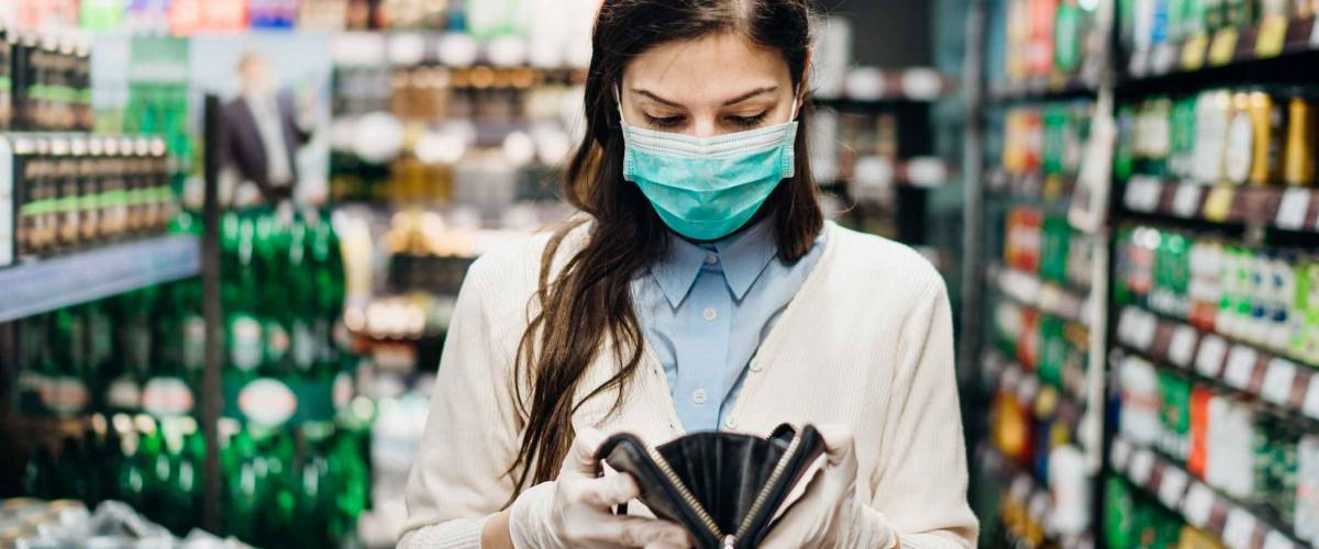 Worried woman with mask groceries shopping in supermarket looking at empty wallet.