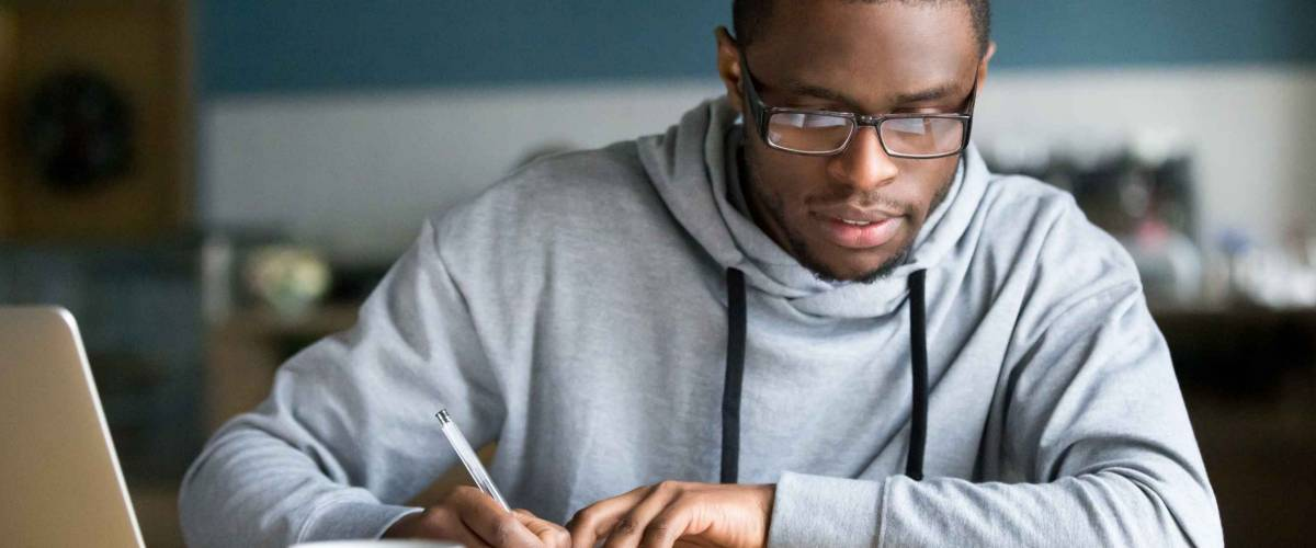 Focused millennial african american student in glasses making notes