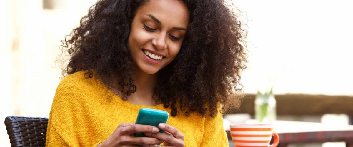 Close up portrait of beautiful young african american woman reading text message on mobile phone at coffee shop