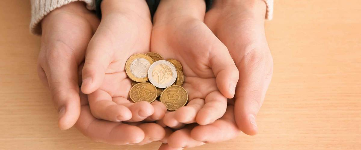 Hands of young man and his son holding coins on wooden table. Concept of child support