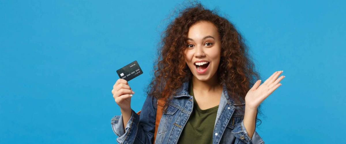 Young african american girl in denim clothes holds credit card