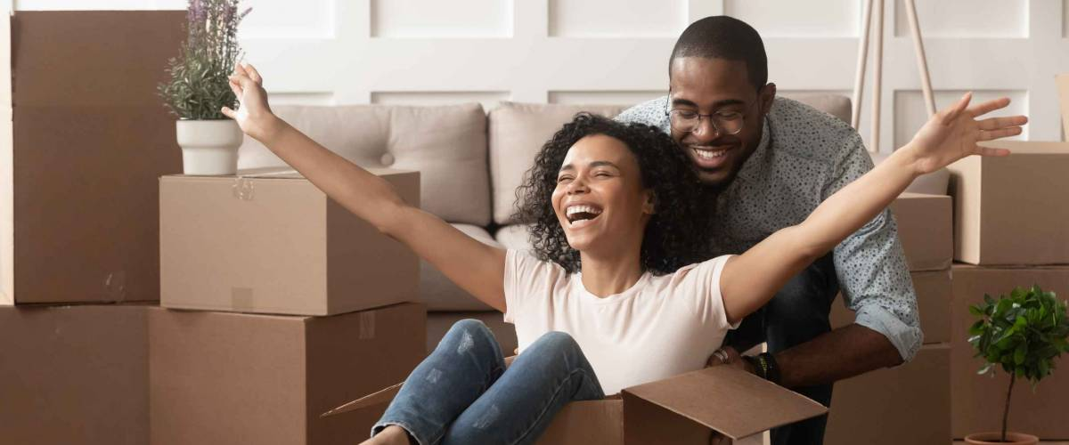 Happy african american young couple first time home buyers having fun unpacking