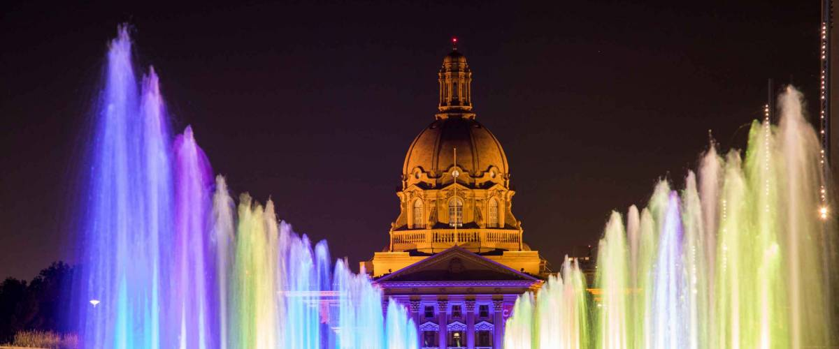 Colorful fountains illuminate a plaza in Downtown Edmonton, Canada, with Alberta's Legislature Building in the background.