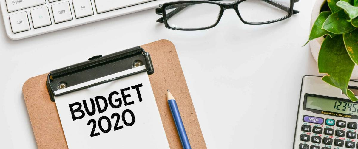 Budget 2020 text concept. Office workplace table with calculator, glasses, textbook and keyboard, budget 2020.