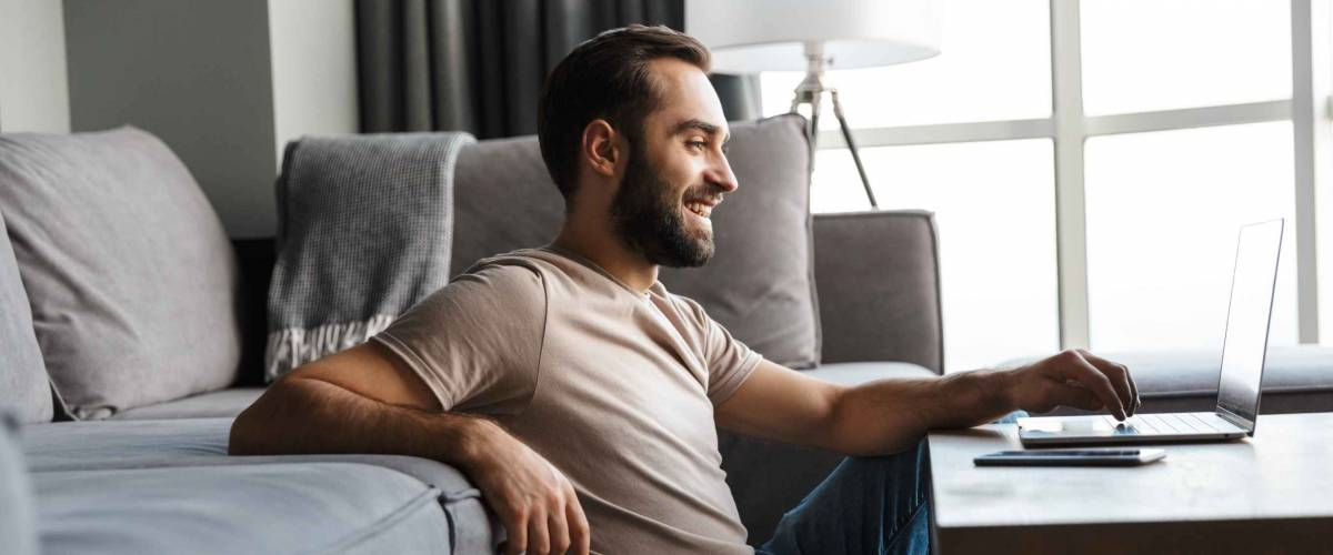 Image of a happy optimistic pleased young man indoors at home using laptop computer.