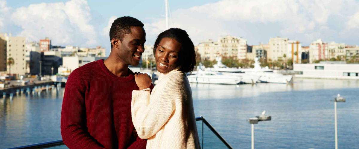 Portrait of happy hugging couple on modern balcony with beautiful port with yachts on background, fashionable couple enjoying each other during vacation holidays in Barcelona