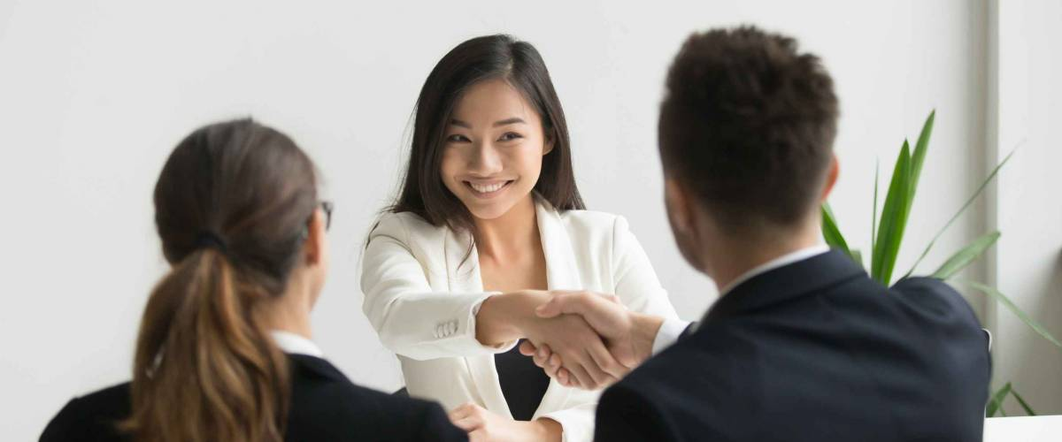 Happy millennial asian applicant getting hired shaking hand
