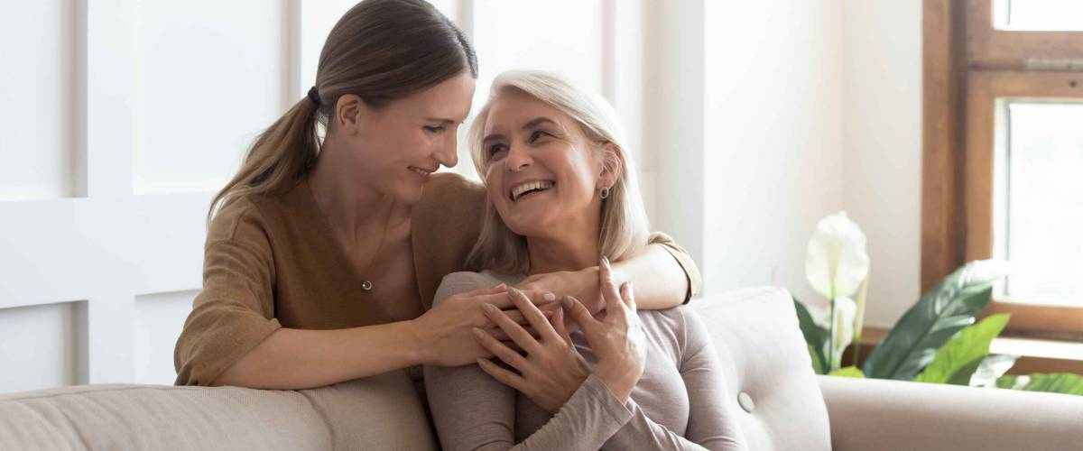 Loving adult daughter hugging older mother, standing behind couch at home