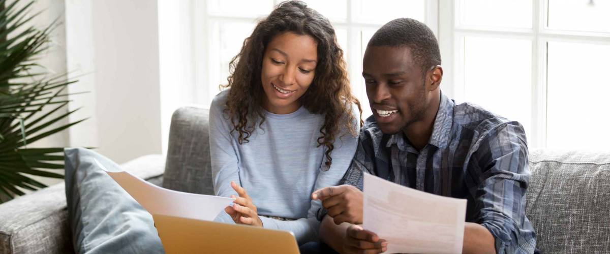 Black positive married couple sitting on sofa at home read documents