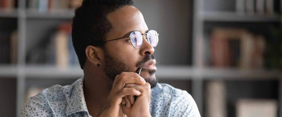 Pensive African American man in glasses distracted from computer