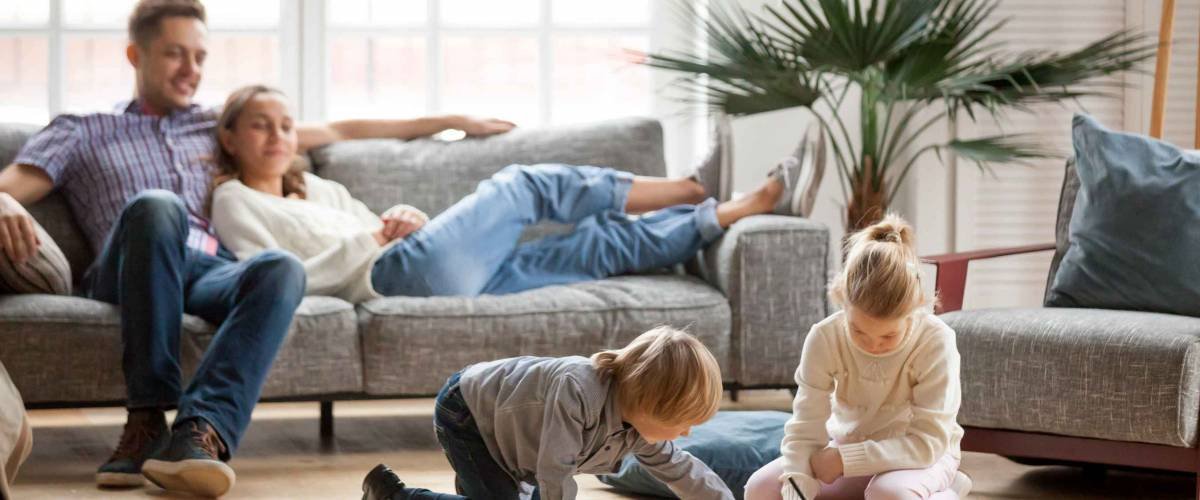 Children sister and brother playing drawing together on floor while young parents relaxing at home