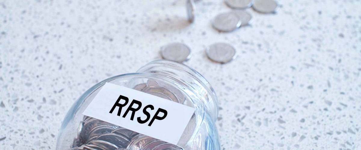 Glass jar with many coins and RRSP word over a marble counter top.Canadian Registered Retirement Savings fund concept.