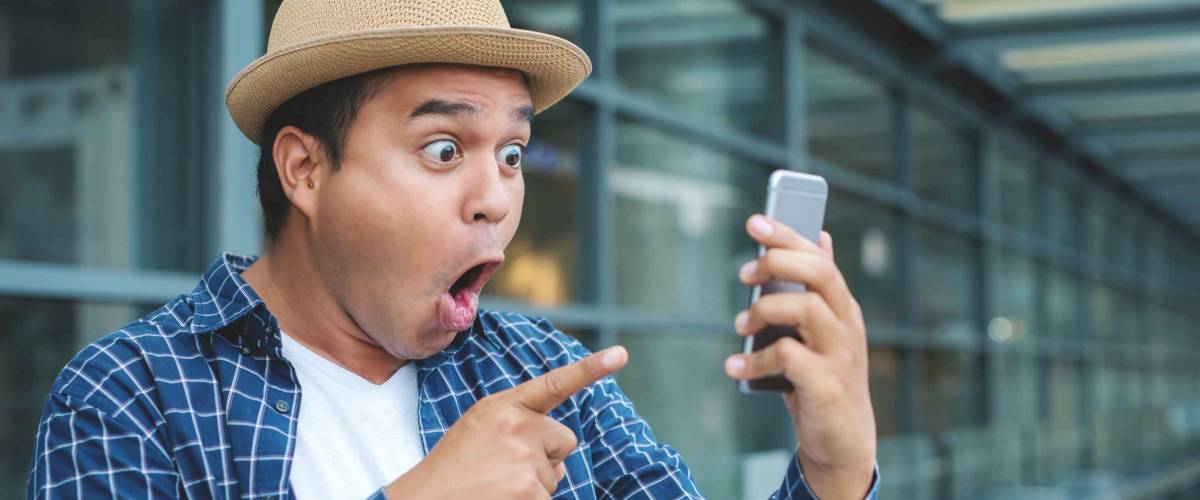 Asian man looking smartphone and shocked