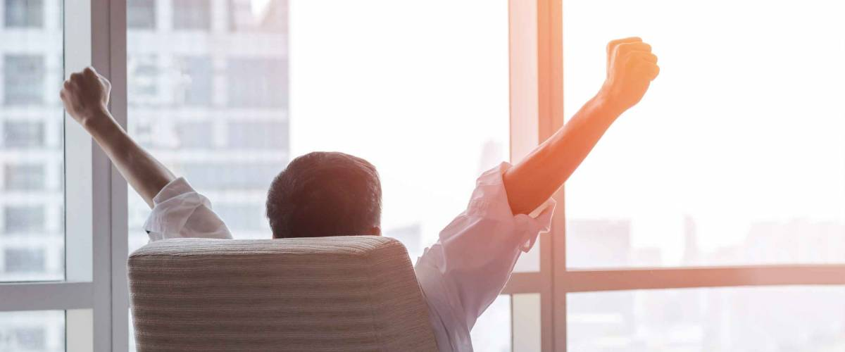 Business achievement concept with happy  businessman relaxing at work in office room, resting and raising fists
