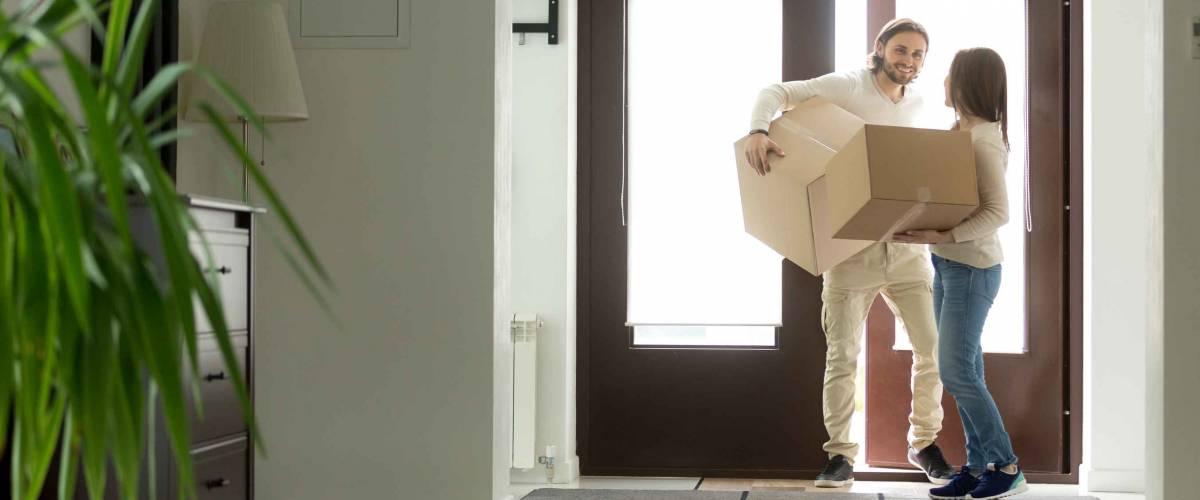 Heureux jeune couple transportant des boîtes en carton ouvrant la porte entrant à l'intérieur de sa propre maison moderne, excité les propriétaires de famille mariés emménageant dans une nouvelle maison, l'achat de biens immobiliers, un prêt hypothécaire