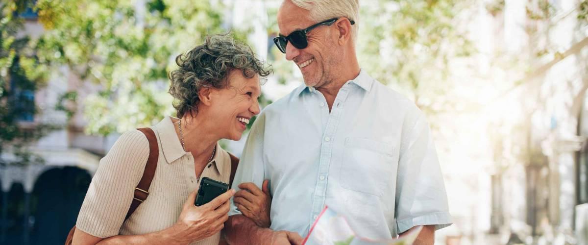 Couple de retraités se promenant dans la ville avec une carte.  Homme d'âge mûr souriant et femme errant dans la ville.