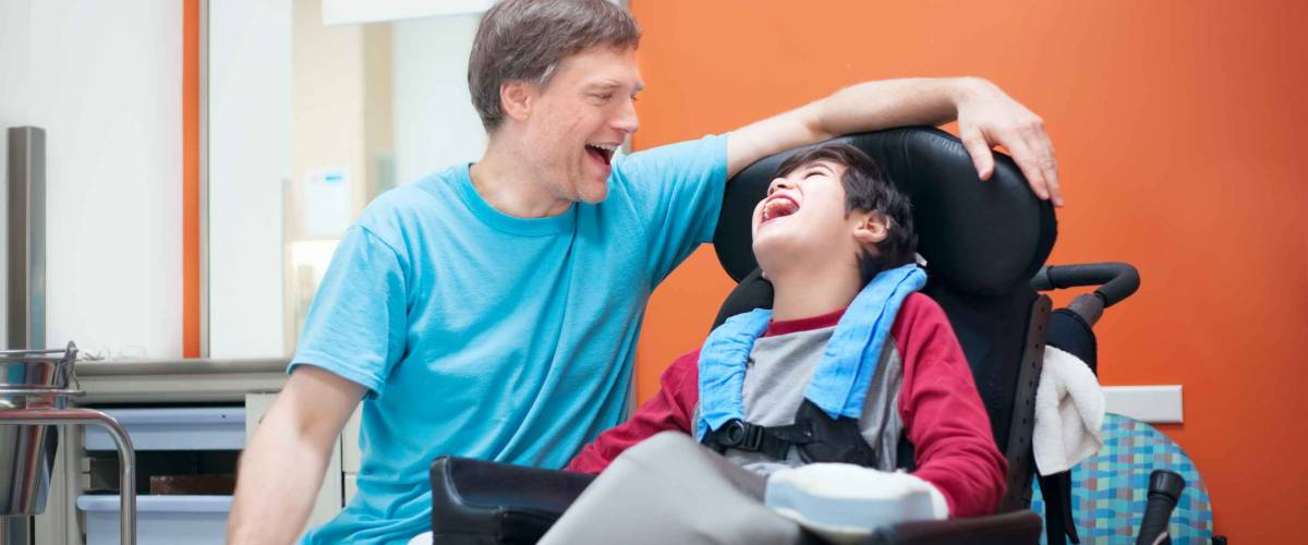 Father talking with disabled biracial son sitting in wheelchair while waiting in doctor's office, laughing together.