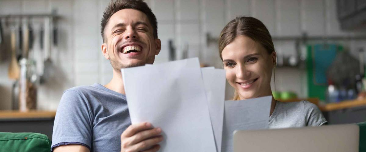 Happy millennial couple laughing reading good positive funny information in paper bills or letters, young smiling man and woman