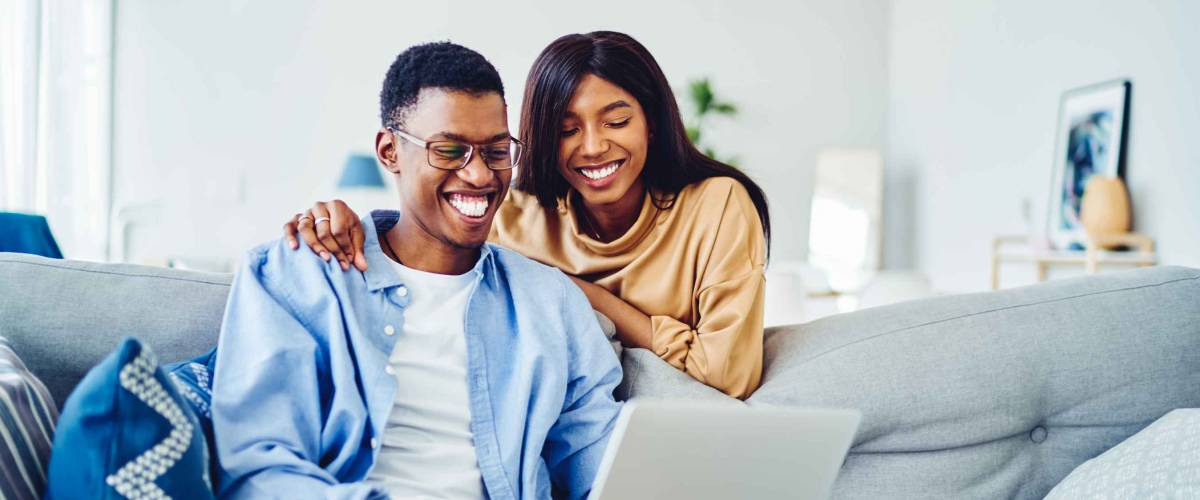 Cheerful African American couple look at laptop