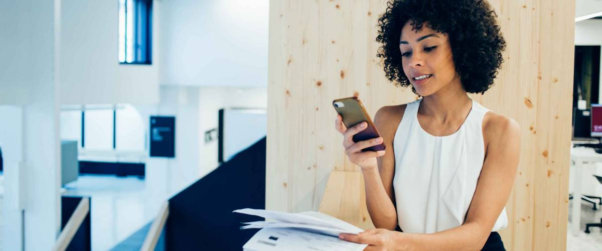 Young woman looking at her phone paying bills