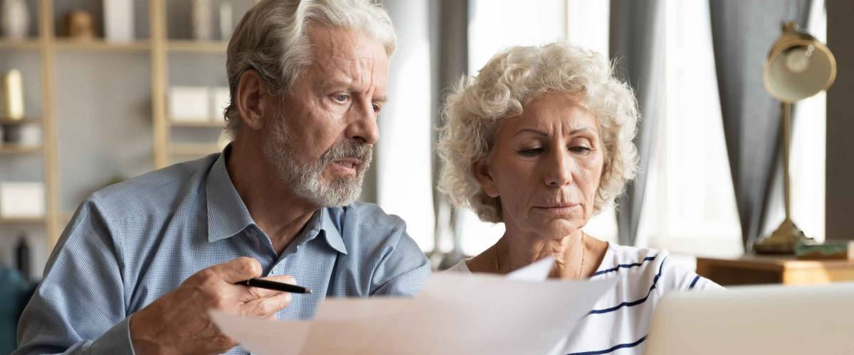 Stressed elderly married couple sitting at table at home having financial problem, bad credit rating.