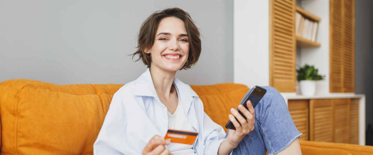 Young woman in casual clothes sitting on couch using mobile cell phone, holding credit bank card