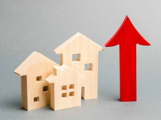 Miniature wooden houses and red arrow up, signifying rising mortgage rates.