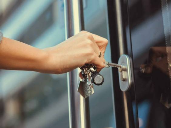 Close-up of a woman unlocking the front door with a key.  Person using the key and locking the apartment door.
