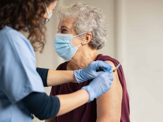 General practitioner vaccinating old patient in clinic with copy space. Doctor giving injection to senior woman at hospital. Nurse holding syringe before make Covid-19 or coronavirus vaccine.