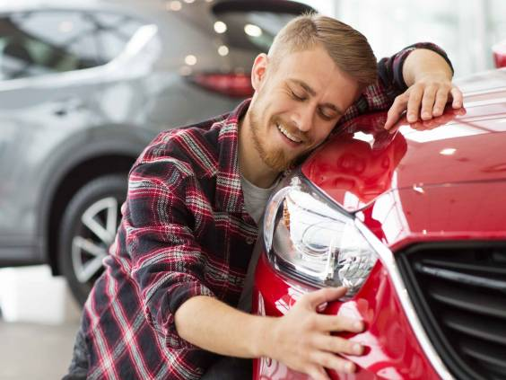 Shot of a handsome young happy bearded man embracing his new car at the dealership smiling joyfully with his eyes closed copyspace happiness love travelling vehicle automotive transport.