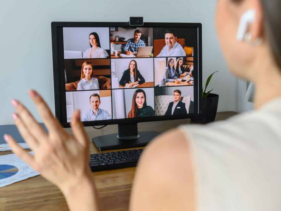 Woman in virtual meeting with colleagues.