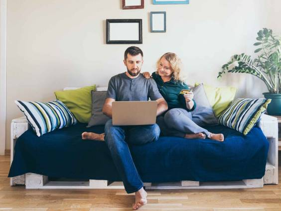Young Caucasian couple doing shoppings online on the couch at home, looking at laptop screen and smiling