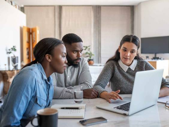 Financial planner going over savings plans on a laptop with a young African American couple at a table in their living room at home
