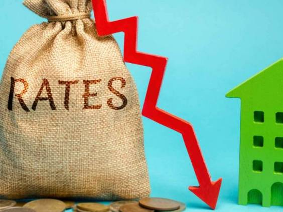 Money bag with the word Rates, down arrow and wooden house. The concept of reducing interest rates on mortgages. Low rental rate for housing. Real estate market and loan.