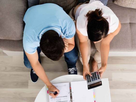 High Angle View Of Young Couple Sitting On Sofa Calculating Budget At Home