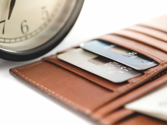 Credit cards in a wallet with a clock in the background.