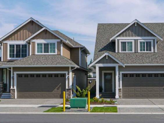 Brand new residential houses with concrete driveway and asphalt road in front