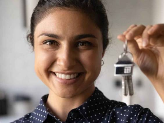 Close up portrait of smiling millennial Indian woman hold show keys to new house.