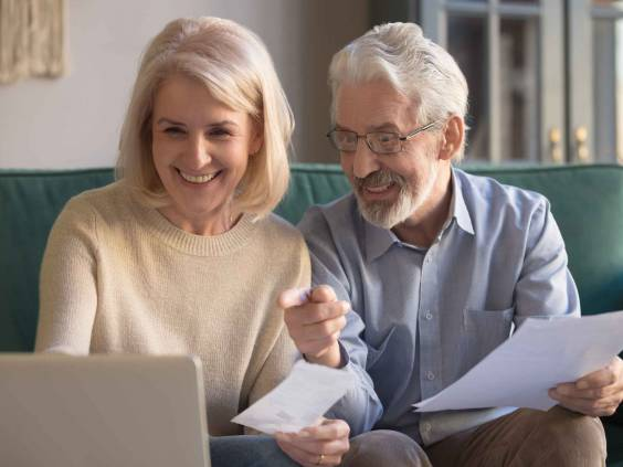 Happy old retired couple paying domestic bills online using computer app