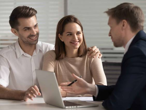 Smiling young family couple consulting with financial advisor.