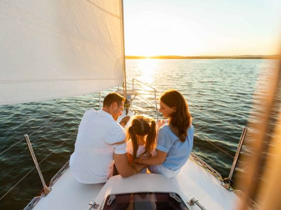Family Yacht Sailing. Parents And Little Daughter Sitting Together On Sailboat Deck Hugging Enjoying Sea Trip. Back View, Free Space