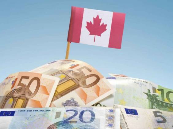 The national flag of Canada sticking in a pile of mixed european banknotes.(series)