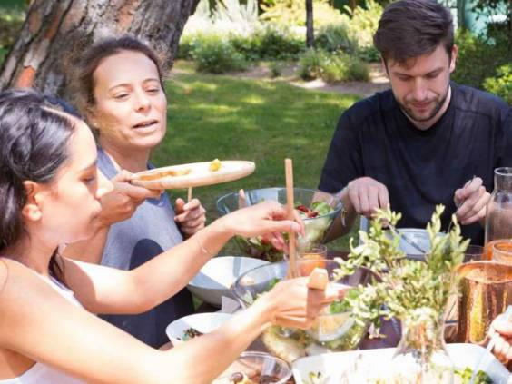 Portrait of serious young people having lunch outdoors. Friends sitting at table and eating together in garden. Outdoor party concept